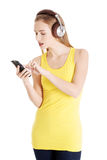 Beautiful casual woman in yellow top is listening to music. Royalty Free Stock Photography