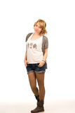 Beautiful casual young blonde woman. Standing with her hands in her pockets wearing shorts and boots, full length studio portrait on white Stock Image