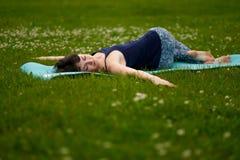 Beautiful caucaisan young woman working out outdoors on blue mat. Jathara Parivartanasana top view. Beautiful caucaisan young woman working out outdoors on blue Stock Image