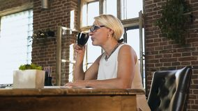 Beautiful caucasian adult woman is holding a cup with hot coffee while works at workplace. Business woman sitting in. Office drinks hot coffee during lunch stock footage