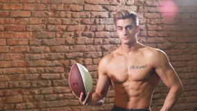 Beautiful Caucasian American football player posing with a ball.