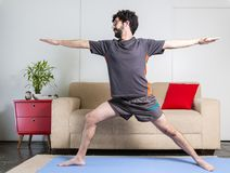 Beautiful caucasian bearded man in black clothes on blue yogamat doing warrior II pose royalty free stock photography