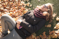 Beautiful Caucasian blond teenage girl laying in park Royalty Free Stock Photos