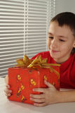 Beautiful caucasian boy holding a gift Royalty Free Stock Image