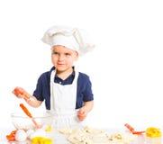 Beautiful caucasian boy making a cake Stock Photos