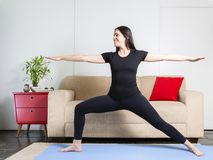 Beautiful caucasian brunette woman in black clothes on blue yoga royalty free stock photo