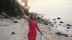 Pretty joyful brunette woman playing with soap bubbles on tropical beach at sunset time. slow motion. 1920x1080. Beautiful Caucasian brunette woman playing with stock video