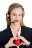 Beautiful caucasian business woman at call center holding heart. Royalty Free Stock Image