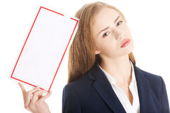 Beautiful caucasian business woman is holding empty white board. Stock Photography