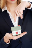 Beautiful caucasian business woman is holding house model. Stock Photo