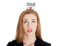 Beautiful caucasian business woman with house model on head. Royalty Free Stock Photography