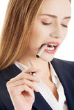 Beautiful caucasian business woman with pen, standing and thinki Royalty Free Stock Photo
