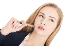 Beautiful caucasian business woman with pen, standing and thinki Stock Image
