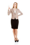 Beautiful caucasian business woman is pointing up. Royalty Free Stock Photo
