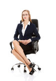 Beautiful caucasian business woman is sitting on a chair with he Stock Photos