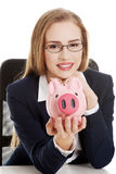 Beautiful caucasian business woman is sitting with piggy bank. Royalty Free Stock Images