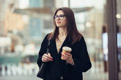 Beautiful caucasian businesswoman walking to the office on city street with coffee cup wearing eyeglasses. royalty free stock image