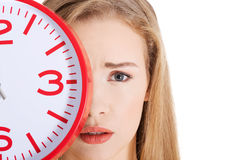 Beautiful caucasian casual woman holding red clock. Royalty Free Stock Photography