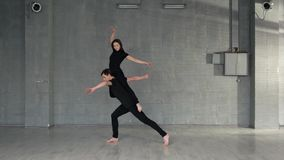 Beautiful caucasian couple performing modern dance. Contemporary style dancers working out in studio. Dance moves practice stock footage