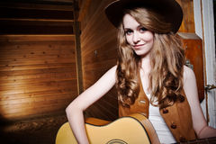 Beautiful caucasian cowgirl with guitar Royalty Free Stock Photography