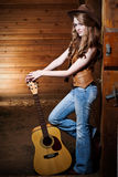 Beautiful caucasian cowgirl with guitar Royalty Free Stock Images