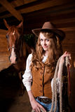 Beautiful caucasian cowgirl with a horse. A portrait of a happy beautiful caucasian cowgirl with a horse Stock Images