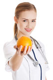Beautiful caucasian doctor or nurse holding an orange. Stock Photos