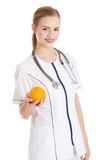 Beautiful caucasian doctor or nurse holding an orange. Royalty Free Stock Photography