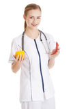 Beautiful caucasian doctor or nurse is holding an orange and chi Stock Photography