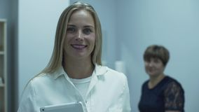 Cute professional caucasian doctor smiling in foreground looking at the camera while her mature patient sitting in stock footage