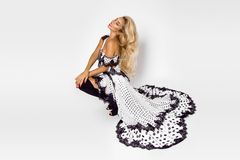 Beautiful caucasian fashion model wearing a white dress with black polka dots on a white background in the studio. Beautiful caucasian fashion model wearing a stock photography