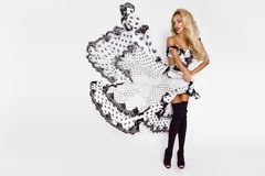 Beautiful caucasian fashion model wearing a white dress with black polka dots on a white background in the studio. Beautiful caucasian fashion model wearing a royalty free stock photography