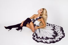 Beautiful caucasian fashion model wearing a white dress with black polka dots on a white background in the studio. Beautiful caucasian fashion model wearing a royalty free stock photos