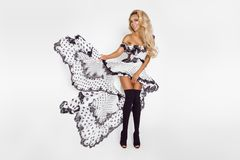 Beautiful caucasian fashion model wearing a white dress with black polka dots on a white background in the studio. Beautiful caucasian fashion model wearing a royalty free stock image