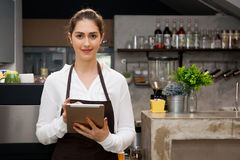 Beautiful Caucasian female barista using tablet and smiling inside coffee shop.  Royalty Free Stock Photos