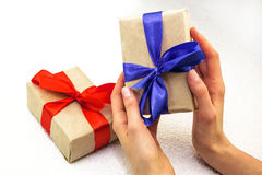 Beautiful caucasian female hands with gift boxes with red and bl Royalty Free Stock Photos