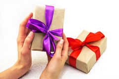 Beautiful caucasian female hands with gift boxes with red and pu Stock Images
