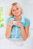 Beautiful caucasian female sitting at table and drinking coffee Royalty Free Stock Photography