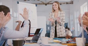 Beautiful Caucasian female team leader gives high five to happy African American female employee at multiethnic meeting.