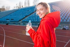 Beautiful Caucasian girl athlete holds in her hands a water in a plastic bottle royalty free stock image