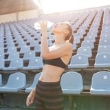 Beautiful Caucasian girl athlete holds in her hands a water in a plastic bottle stock image