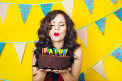 Beautiful caucasian girl blowing candles on her cake. Celebration and party. Having fun. Young pretty woman in red dress and birth. Day hat is laughing Stock Photo