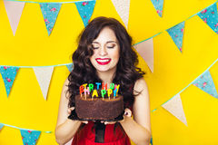Beautiful caucasian girl blowing candles on her cake. Celebration and party. Having fun. Young pretty woman in red dress and birth. Day hat is laughing Stock Images