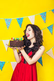 Beautiful caucasian girl blowing candles on her cake. Celebration and party. Having fun. Young pretty woman in red dress and birth. Day hat is laughing Royalty Free Stock Images