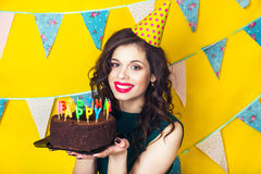 Beautiful caucasian girl blowing candles on her cake. Celebration and party. Royalty Free Stock Images