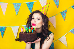 Beautiful caucasian girl blowing candles on her cake. Celebration and party. Stock Photos