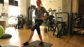 Step lunges exercises. Beautiful caucasian girl doing stretching exercises legs indoor on step. Girl doing lunges stretching. Fit fitness sports model exercising stock video footage