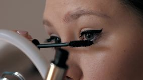 Beautiful caucasian girl dyeing her eyelashes with a large brush. fashion industry cosmetics. Close-up of beautiful caucasian girl dyeing the eyes with a large stock video