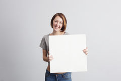 Beautiful caucasian girl holding a blank poster for text or ad. Stock Photography