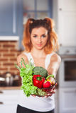 Beautiful caucasian girl holding glasses bowl with ingredients for low-caloric vegetables salad on kitchen. Selective focus. Vertical royalty free stock image